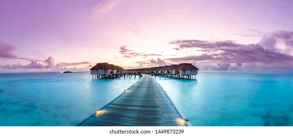 Amazing panorama beach landscape. Maldives sunset seascape view. Horizon with sea and sky. Tranquil scenery, tourism and travel banner. Summer  luxury resort landscape, vacation holiday island concept