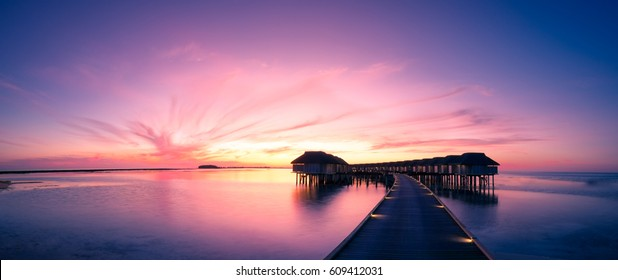 Amazing panorama beach landscape. Maldives sunset seascape view. Horizon with sea and sky. Tranquil scenery, tourism and travel banner