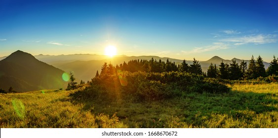 Amazing panorama of dawn in the mountains. The sun rises on the peaks of distant mountains, illuminating conifers and green grass of mountain slopes
