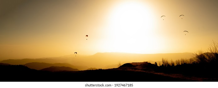 Amazing panorama silhouette of paragliding in landscape with mountains at sunset and yellow sky