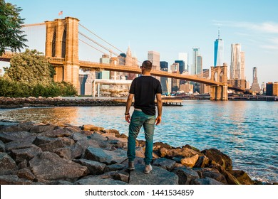 Amazing panorama view of New York City skyline and Brooklyn bridge looked by tourist with skyscrapers and East River flowing during daytime in United States of America