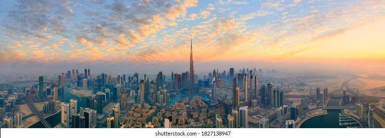 Amazing panoramic view of Dubai skyline showing the world's tallest building, Burj Khalifa, during sunset, vibrant skies with clouds in futuristic city downtown; Perfect travel destination panorama