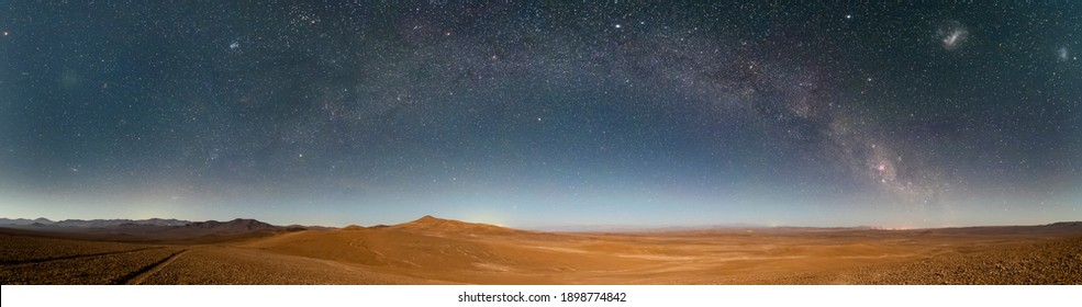 An amazing panoramic view of the Milky Way above Atacama Desert vast sand fields. An awe night sky view with our galaxy arm creating an arch in between the stars. An idyllic and motivational scenery