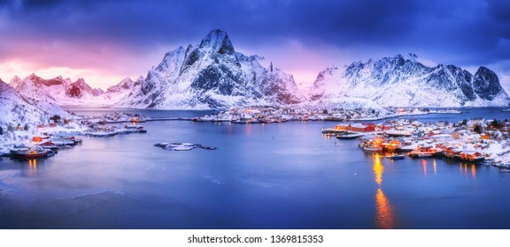 Amazing panoramic view on lovely arctic village Reine on Lofoten islands in Norway, Scandinavia, Europea. Beautiful polar peaks and dramatic sunset sky in background.