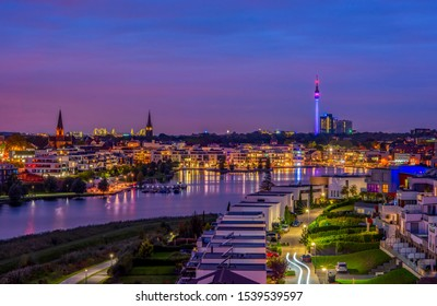 Amazing panoramic view of Phoenix Lake in Dortmund, Germany over city skyline and Florian Tower illuminated at twilight. It is an artificial lake and recreational area on the former steelworks