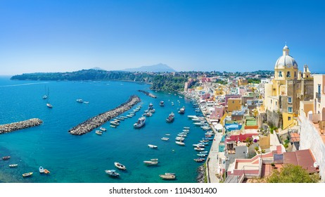 Amazing panoramic view of Procida in sunny summer day. Colorful houses, cafes and restaurants in Marina Corricella, clear blue sky and sea in Procida island, Italy.