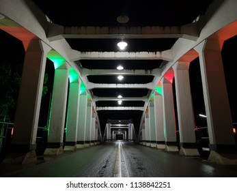 Amazing perspective and vanishing point with old white bridge at night,  asphalt wet road surface, Ratchadapisek Bridge in Lampang, Thailand