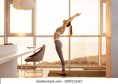 Amazing photo of young  lady in sporty top and leggings standing and practicing yoga on yoga mat at home with big beautiful windows on background