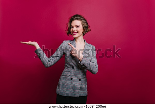 Amazing pleased curly woman in gray jacket posing in studio. Laughing brunette girl isolated on claret background happy smiling. Place for text