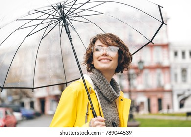 Amazing portrait of happy woman in yellow raincoat walking in city under transparent umbrella, during cold rainy day