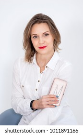Amazing Pretty Female Cosmetician with Sensual Red Lips is Holding Instruments for Beauty Treatments in Studio on White Background.