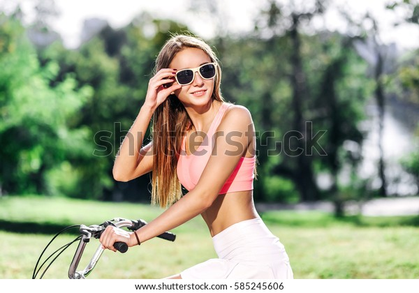 amazing pretty woman ride bicycle and in  glasses chic outfit,denim clothes,hipster girl, sunglasses fashion,urban street style,soft  colors,rider  bicycle.relax
