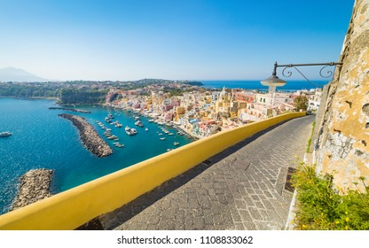 Amazing Procida in sunny summer day. Colorful houses, cafes and restaurants in Marina Corricella, clear blue sky and sea in Procida island, Italy.