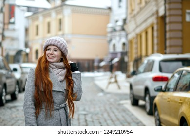 Amazing red head woman wearing winter cap and coat pwalking at the city. Space for text