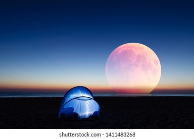 Amazing red moon over the sea, beach and lit tent at sunrise