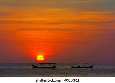 Amazing red sun sunset with fisherman's boats silhouettes, Kuta beach, Bali