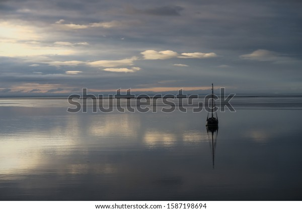 Amazing reflection of a small sailing ship in the bay of tadoussac on the saint lawrence river on a cloudy day