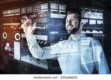 Amazing results. Professional young enthusiastic programmer smiling and feeling satisfied with amazing results of his team while looking at the transparent screen
