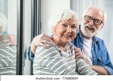 Amazing retirement. Waist up portrait of two old cheerful pensioners smiling at camera. Husband is tenderly hugging wife while sitting at window