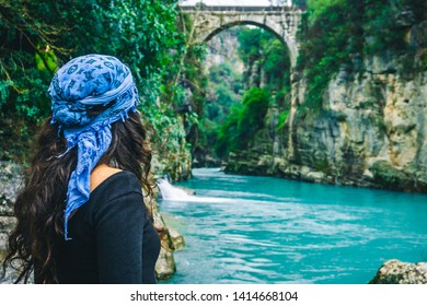 Amazing river and ancient bridge landscape from Koprulu Canyon in Manavgat, Antalya, Turkey. A woman watching the old bridge on river. Holiday and tourism concept