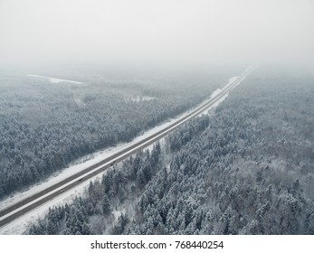 Amazing road in the frozen winter forest with driving cars. Foggy vanishing point perspective. Aerial panoramic view on the north.