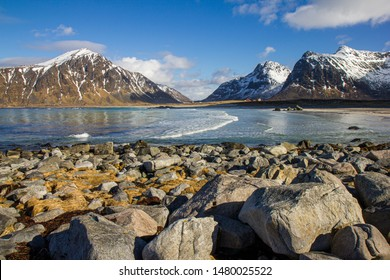 Amazing rocky beach and snow covered peaks of mountain range in the background. Pure natural beauty of Norway.