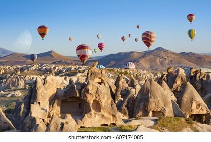 Amazing rocky landscape in Cappadocia. Hot air balloons fly in clear morning sky near Goreme, Kapadokya, Turkey