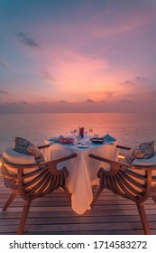 Amazing romantic dinner on the beach on wooden deck with candles under sunset sky. Romance and love, luxury destination dinning, exotic table setup with sea view