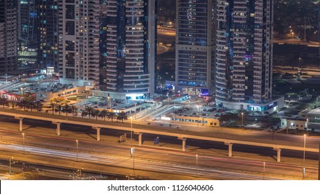 Amazing rooftop view on Sheikh Zayed road surrounded Dubai Marina and JLT skyscrapers, Dubai. Aerial view at night with traffic and metro line. United Arab Emirates