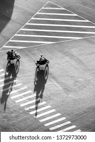 Amazing scene on street at Asian city from high view, group of Vietnamese people ride motorcycles moving with shadow on road surface make impression shape
