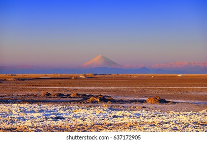 Amazing scenery: colorful sand, white salt, blue sky, distant mountain range and Damavand mount (Demavend volcano), the highest peak of Middle East, view from Maranjab desert, Aran va Bidgol, Iran