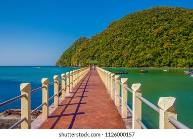 Amazing scenery of Pulau Dayang Bunting's jetty (Island of the Pregnant Maiden) with a beautiful lush green mountain backdrop, blue & turquoise water; tourists waiting to be picked up by motorboats.