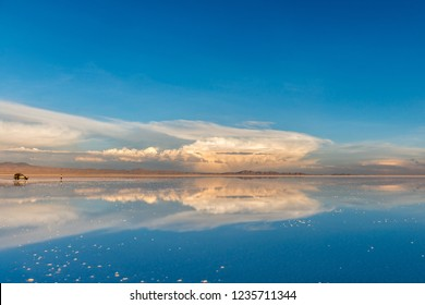 Amazing scenery of the spacious Salar de Uyuni with car on it and exciting blue sky reflection on mirror surface
