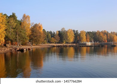 Amazing scenic landscape of Matinkylä beach located in Espoo, Finland. In this photo you see yellow and green trees during fall / winter and their reflections on a calm sea just before a sunset.