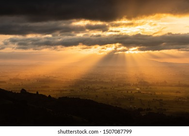 Amazing scenic sunset over endless rolling hills, villages and lakes. Beautiful sun rays peaking through the clouds. Colorful and vivid scene, peaceful and relaxing.
