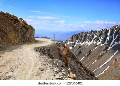 Amazing scenic view of high mountain road in rugged rock covered with melting snow against the background of dramatic blue sky, Leh district, Ladakh range, Himalayas, Jammu & Kashmir, Northern India