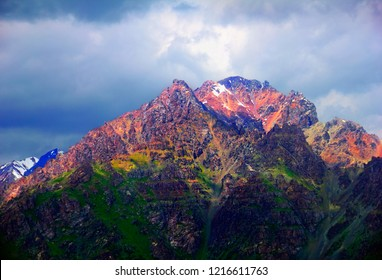 Amazing scenic view of rugged colorful mountain covered with green moss and settled by the last sun rays against the background of dark cloudy evening sky, Tien Shan range, Kyrgyzstan, Central Asia