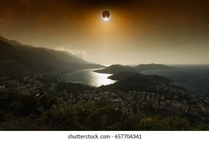 Amazing scientific background - total solar eclipse in dark red glowing sky above seaside city, mysterious natural phenomenon when Moon passes between planet Earth and Sun.