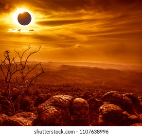 Amazing scientific natural phenomenon. The Moon covering the Sun. Total solar eclipse with diamond ring effect glowing on sky above wilderness area with mountain range. Serenity nature background.