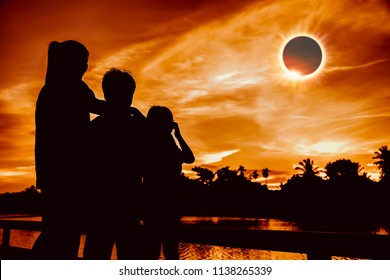Amazing scientific natural phenomenon. The Moon covering the Sun. Silhouette of mother and children looking at total solar eclipse with diamond ring effect on sky. Happy family spending time together.