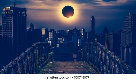 Amazing scientific natural phenomenon. The Moon covering the Sun. Total solar eclipse with diamond ring effect glowing on sky above skyscrapers with old concrete bridge. Serenity nature background.