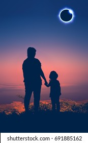 Amazing scientific natural phenomenon. Silhouette back view of Mother and daughter looking at total solar eclipse with diamond ring effect glowing on colorful sky at mountaintop. Happy family.