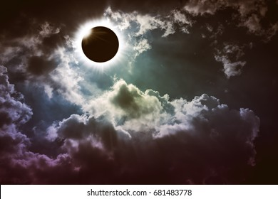 Amazing scientific natural phenomenon. Total solar eclipse with diamond ring effect glowing on sky with dark clouds. Abstract fantastic background of beautiful nature and serenity landscape.