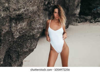 6b98fefc1 Amazing sexy girl in white swimsuit with perfect sporty body and curly  hairs relaxing at the