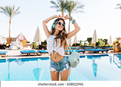 Amazing shapely girl in white blouse dancing with hands up, while listening positive music near the pool. Young tanned woman in headphones and sunglasses having fun on palm trees background