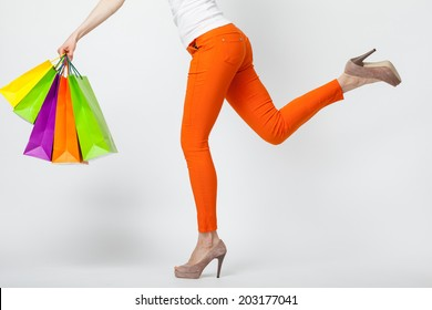 Amazing shopping! Unrecognizable woman in orange pants running with multicolored shopping bags