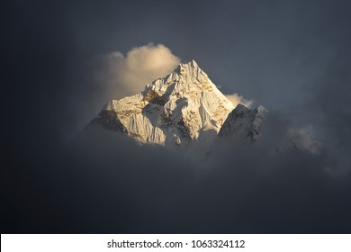 Amazing shot of Ama Dablam mountain peak (6812m) covered with white snow and surrounded with light clouds. Nepalese Himalayas