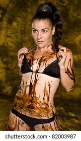 amazing shot of a young beautiful brunette with her naked body covered of sweet cream chocolate