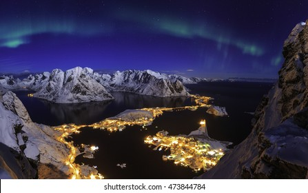 Amazing show of the colored northern lights over the scenic small village, viewed from the Norwegian peak covered in snow, Reinebringen, Lofoten, Norway
