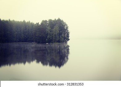 Amazing and silent morning by the lake. A small island is reflecting it's treeline on a still water. Image has a vintage effect applied.
